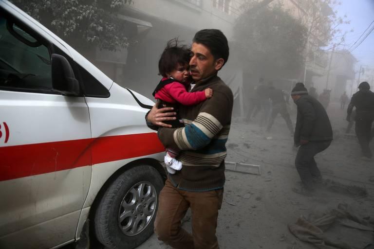 Sírio carrega criança após bombardeio do regime sírio em Ghouta, na região de Damasco, nesta quinta-feira (8)