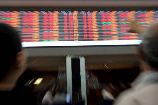 FILE PHOTO: People look at an electronic board on the floor of Brazil's BM&F Bovespa Stock Market in Sao Paulo