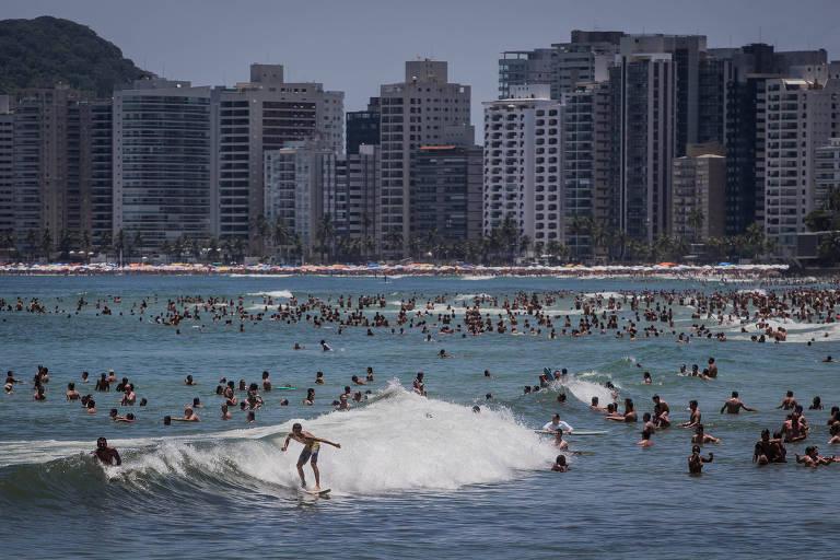 Praia lotada no Guarujá, com banhistas nadando ou surfando