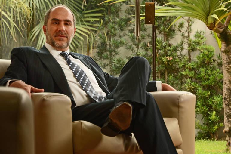 O advogado Jorge Bouchabki sentado com a perna esquerda cruzada sobre a direita. Ele está de terno preto, gravata escura com listas transversais e camisa branca. A poltrona é marrom e ao fundo tem um jardim.