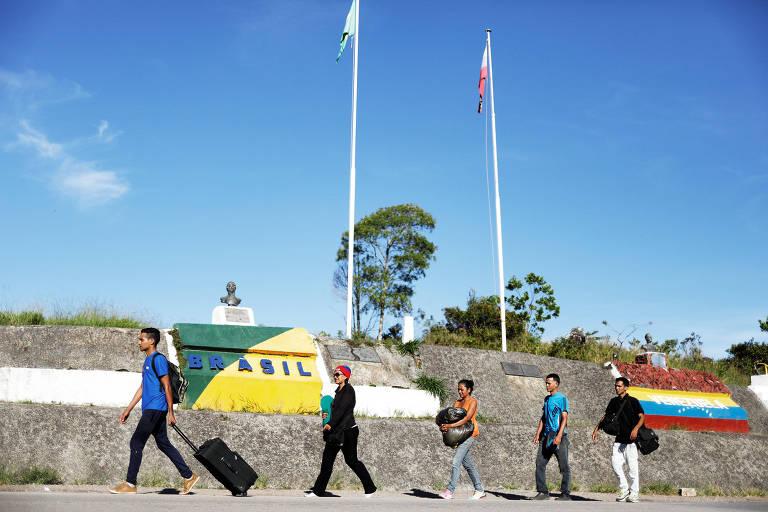Venezuelanos cruzam a fronteira na cidade de Pacaraima (RR); governo vai reforçar segurança na divisa com a Venezuela