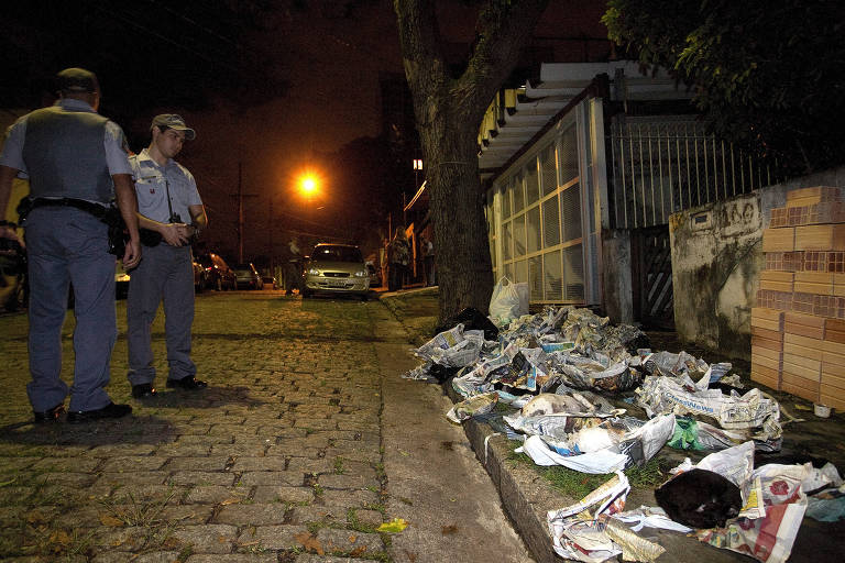 Policiais militares observam bichos mortos após operação na casa de Dalva, em janeiro de 2012
