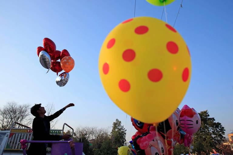 Vendedores infla balões com formato de coração para oferecer a clientes em Islamabad, no Paquistão