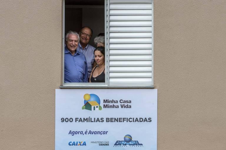 O presidente Michel Temer, o governador Geraldo Alckmin e uma mulher aparecem em janela de prédio do MCMV