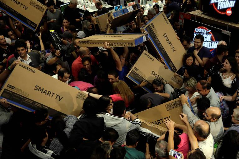 Multidão aglomerada em loja carrega aparelhos de TV