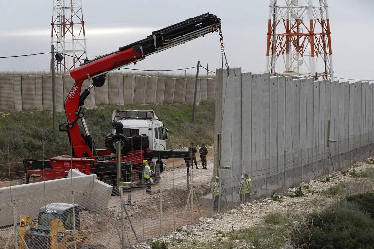 Operários israelenses erguem muro na fronteira do país com o Líbano, perto da cidade libanesa de Naqura