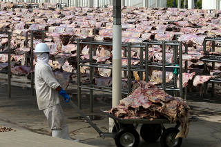 A worker carries salted meat which will be spreaded, dried and then packed at a plant of JBS S.A, the world's largest beef producer, in Santana de Parnaiba