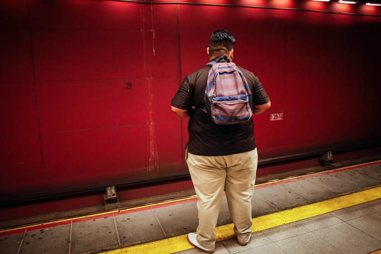 Homem espera por metrô em Santiago, no Chile; em 2018, o país declarou guerra a comidas não saudáveis por causa de epidemia de obesidade; é um homem obeso, visto de costas para a câmera na plataforma da estação, que tem ao fundo uma parede vermelha