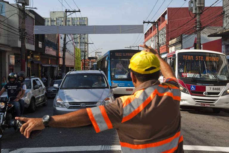 Agente da CET desviam o trânsito de automóveis em São Paulo