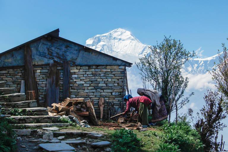 Mulheres cortam lenha em frente a casa, com montanhas com neve ao fundo