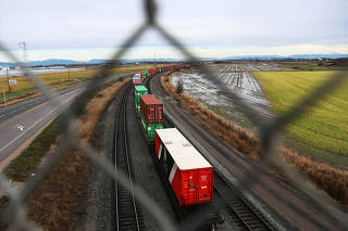 Shipping containers travel on railcars away from Roberts Bank Superport in Delta,