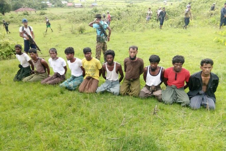 Dez muçulmanos rohingya são vistos ajoelhados e com mãos amarradas ao lado de membros das forças de segurança de Mianmar em  Inn Din
