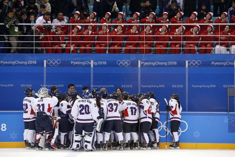 Jogadoras da equipe unificada da Coreia no hóquei feminino se reúnem diante da torcida na partida contra a Suíça