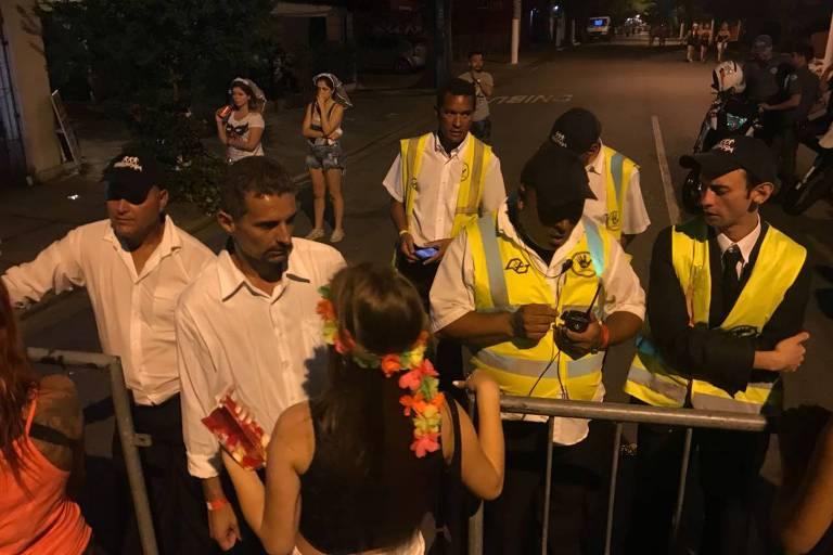 Quatro homens com coletes amarelos impedem mulher de passar por grade colocada em rua da Vila Madalena