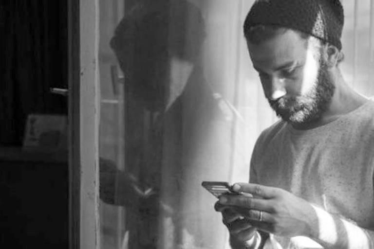 Homem consulta informações pelo celular