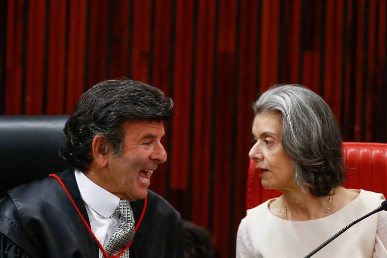 Ministros do STF Luiz Fux e Carmén Lúcia se olham. Fux ri enquanto Carmén Lúcia olha com seriedade para ele.