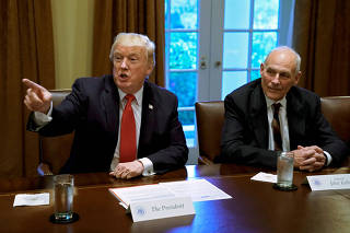 FILE PHOTO: U.S. President Donald Trump gestures next to White House Chief of Staff John Kelly during a briefing at the White House in Washington
