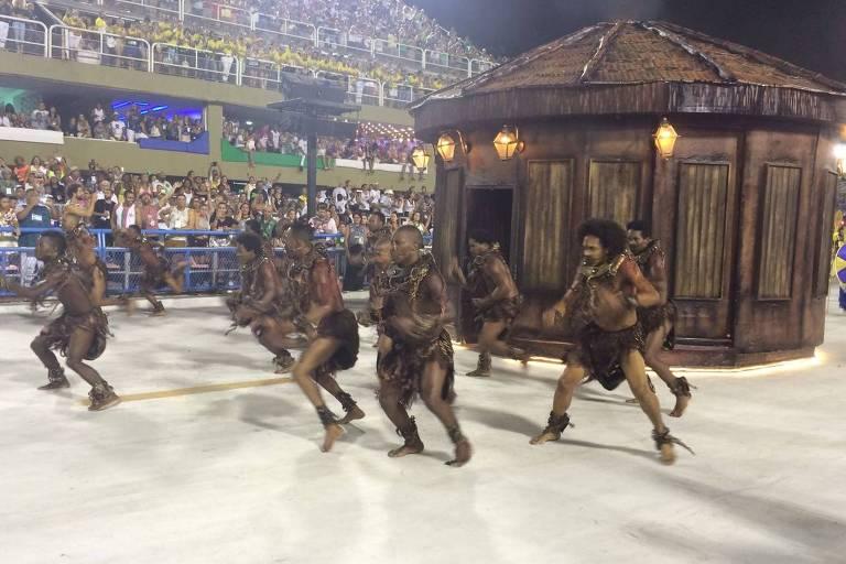 A Paraíso de Tuiuti já está na avenida. A comissão de frente, muito aplaudida pelo público, traz uma coreografia que encena escravos recém-chegados da África amordaçados e levando chibatadas