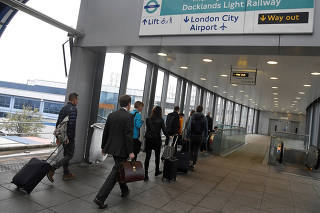 FILE PHOTO: Passengers alight from a train to enter City Airport in London, Britain