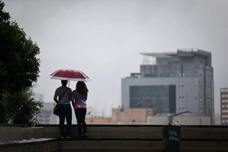 Casal se protege da chuva na região da avenida Paulista, centro de São Paulo