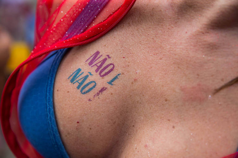 """Decote de mulher com os dizeres """"Não é não!"""" tatuado no peito"""