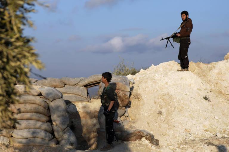 Dois homens com trajes militares camuflados e armados com metralhadoras observam quem chega atrás de uma rocha e barricadas montadas com sacos de areia