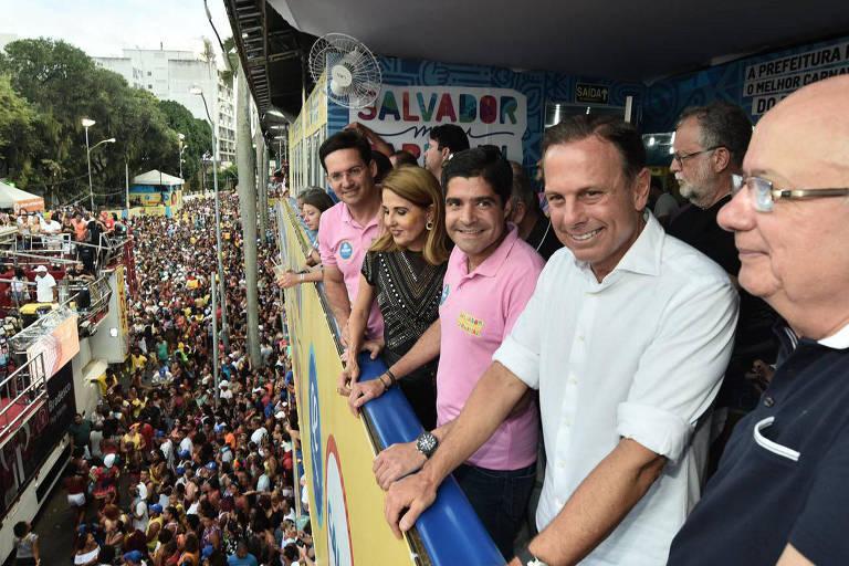 Prefeito de São Paulo, João Doria, de camisa branca, ao lado de ACM Neto, de camisa polo rosa, em camarote no carnaval em Salvador.