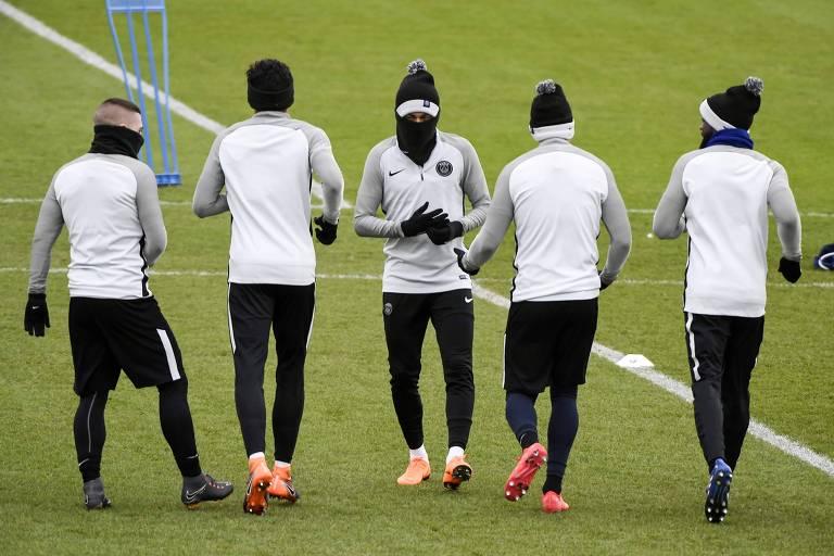 Com rostos protegidos contra frio, jogadores do PSG, com Neymar no centro, treinam na véspera de partida contra o Real Madrid pela Liga dos Campeões