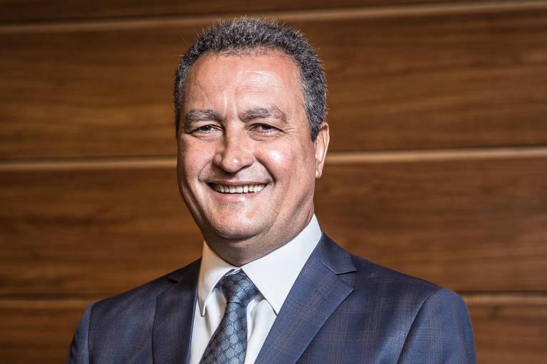 Rui Costa, governador da Bahia, sorri. Está de terno azul escuro, camisa branca e gravata listrada