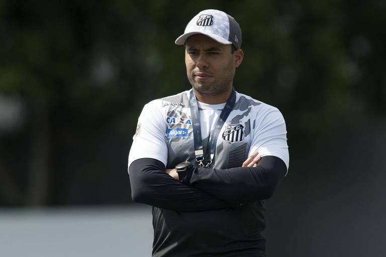Técnico Jair Ventura, de braços cruzados e uniforme do Santos, comanda um treino da equipe no CT Rei Pelé