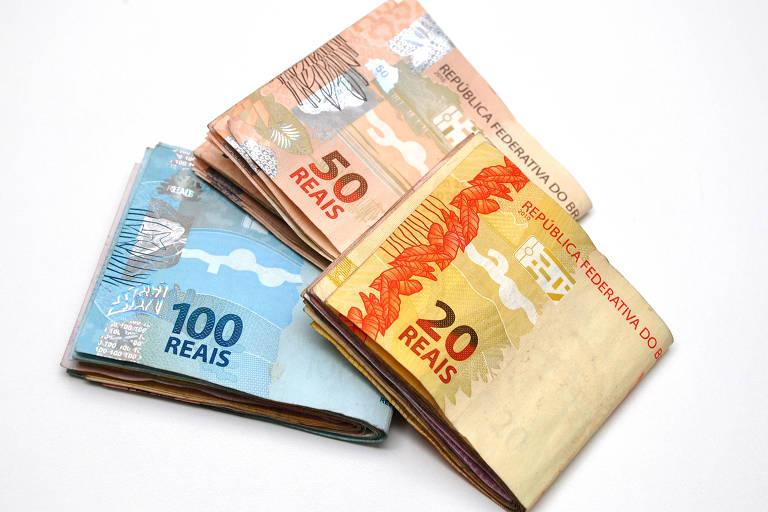 Foto de três maços de dinheiro de R$20, R$50 e R$100