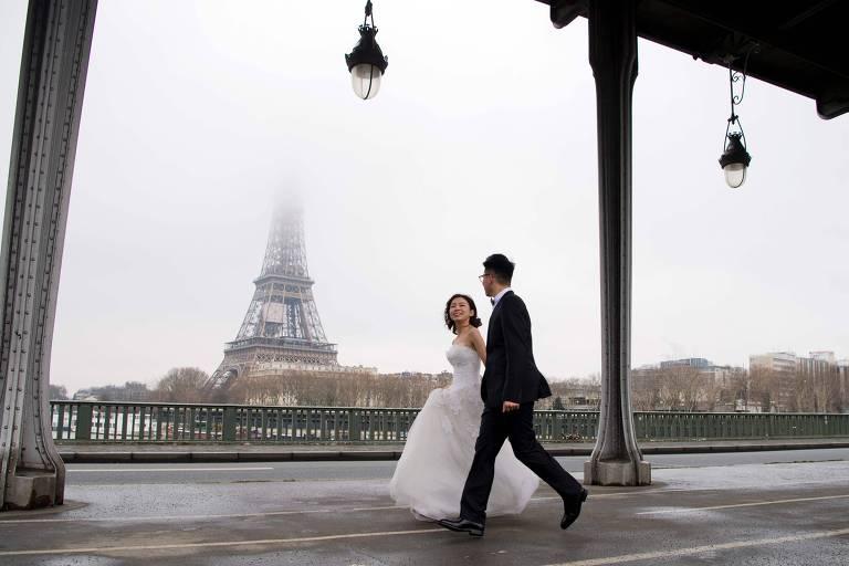 Casal comemora casamento na ponte de Bir-Hakeim, tendo ao fundo a Torre Eiffel, em Paris, na França