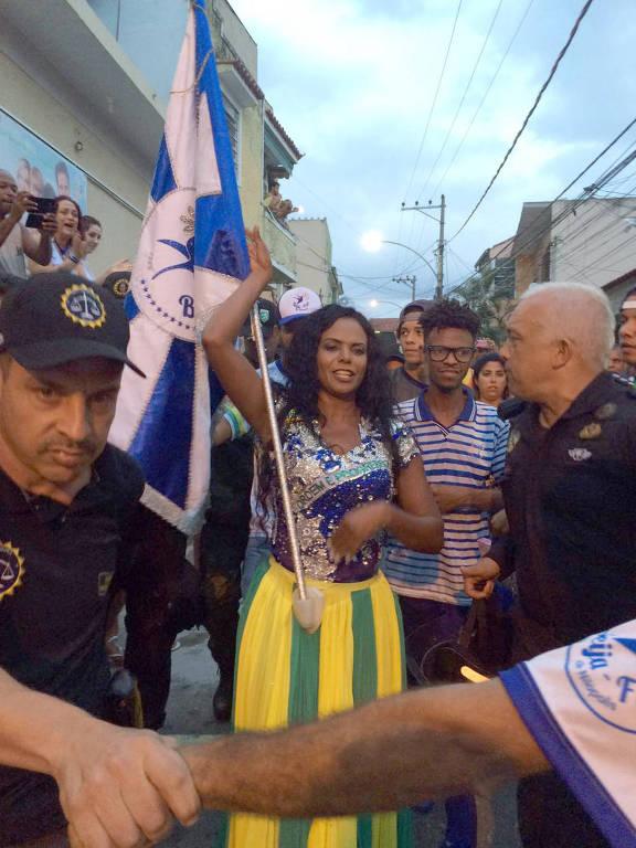A porta-bandeira Selminha Sorriso é escoltada até o palco da Beija-Flor após título