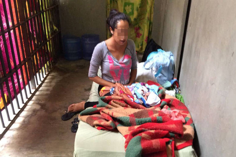 Mãe com o filho recém-nascido em um colchão na cela da carceragem do 8º DP (Brás)