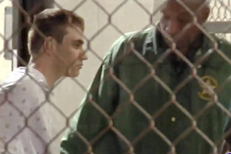 Imagem de TV mostra Nikolas Cruz (esq.) chegando à prisão escoltado por um policial no condado de Broward