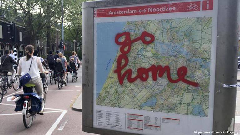 """Mulher anda de bicicleta ao lado de mapa de cidade com a frase """"go home"""" pixada"""