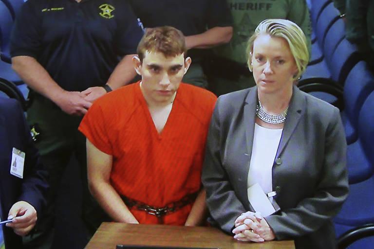 Imagens de câmeras de segurança mostram Nikolas Cruz (de uniforme laranja), ao lado da advogada, no momento em que foi indiciado no tribunal do condado de Broward, na Flórida