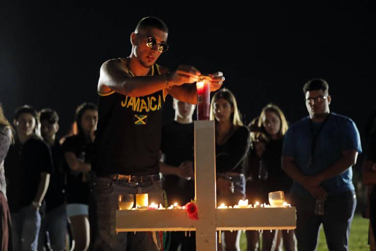 Aluno acende vela em uma das 17 cruzes colocadas pelos colegas das vítimas do ataque à escola Marjory Stoneman Douglas, em Parkland, na Flórida