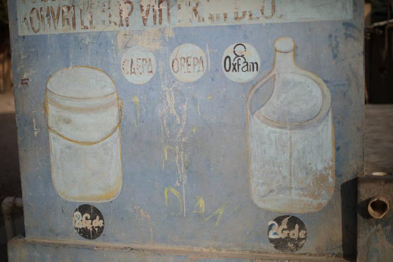 Símbolo da Oxfam é visto ao lado das siglas de outras organizações em um posto de entrega de água em Corail, no Haiti