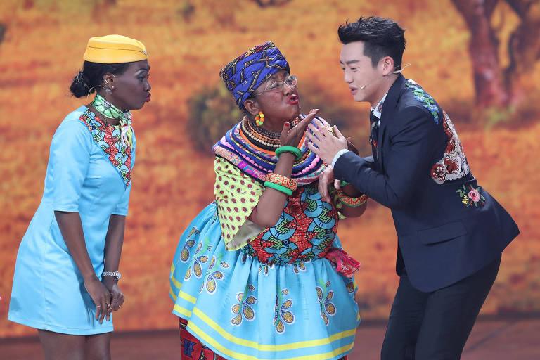 A atriz chinesa Lou Naiming, ao centro, interpreta uma mulher negra em uma cerimônia de comemoração do Ano-Novo Lunar