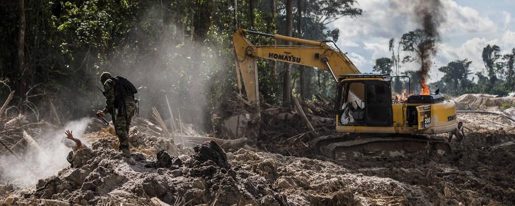 Área de garimpo ilegal na floresta. Ao canto esquerdo da foto, um funcionário do Ibama, vestido de preto, lança spray para se defender de um índio garimpeiro, que está deitado no chão