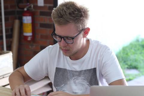Eduardo Hommerding, 26, dono da empresa Dobra, na linha de produção em que faz carteiras de papel impermeável