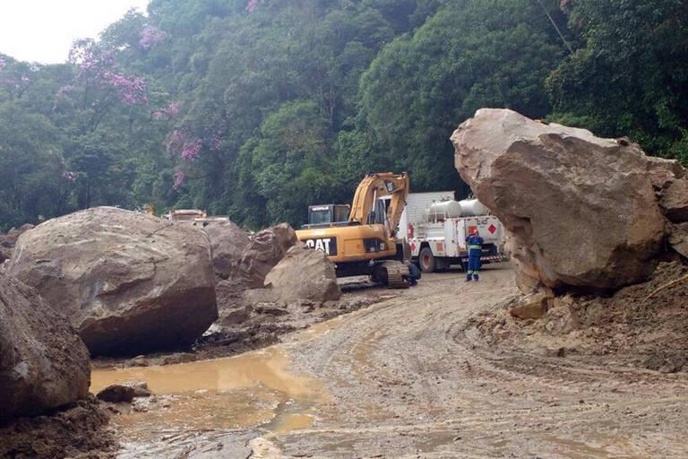Funcionários do DER (Departamento de Estradas de Rodagem) tentam desobstruir a rodovia Mogi-Bertioga, em São Paulo