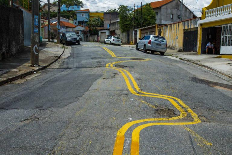 Sinalização em zigue-zague, desviando de buracos, na rua Diogo Botelho, na zona leste de SP