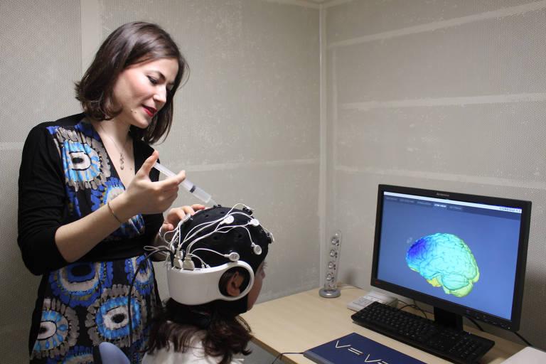 Uma das pesquisadoras faz teste com estimulação elétrica em estudante no laboratório da Universidade Queen Mary, em Londres