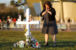 Diana Haneski, a librarian at Marjory Stoneman Douglas High School, pauses near one of the crosses erected for the victims of the school shooting in Parkland