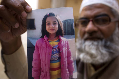 FILE - In this Thursday, Jan. 18, 2018, file photo, Mohammed Amin shows a picture of his seven year-old daughter, Zainab Ansari in Kasur, Pakistan. A public prosecutor in Pakistan says on Saturday, Feb. 17, 2018, a court has sentenced a serial killer to death after finding him guilty of killing eight children, including a 7-year-old girl whose rape and murder drew nationwide condemnation. (AP Photo/B.K. Bangash, File) ORG XMIT: ISL101