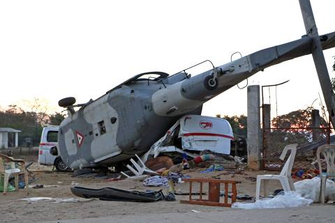 TOPSHOT - View of the remains of the military helicopter that fell on a van in Santiago Jamiltepec, Oaxaca state, Mexico, on February 17, 2018.  A 7.2-magnitude earthquake rattled Mexico on Friday, causing little damage but triggering a tragedy when a minister's helicopter crash-landed on the way to the epicenter, Oaxaca, killing thirteen people, including three children, on the ground. / AFP PHOTO / PATRICIA CASTELLANOS ORG XMIT: YAC2631