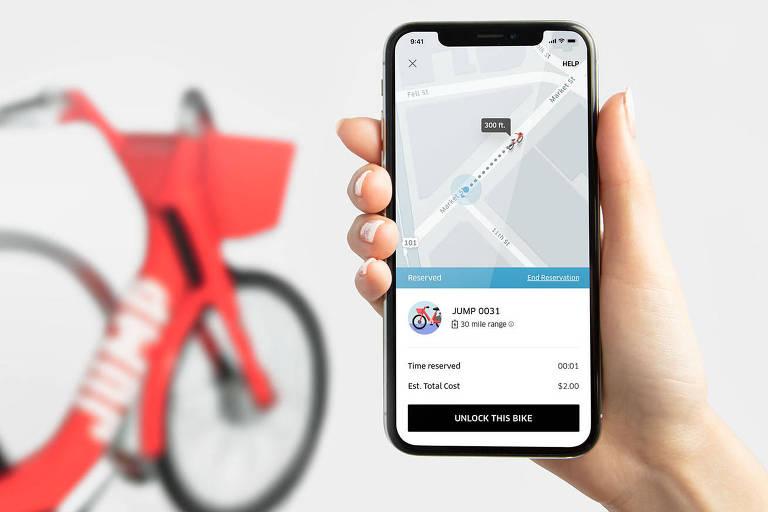 Aplicativo da Uber com bicicleta da JUMP ao fundo