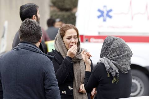Relatives of Iranian passengers, onboard the Aseman Airlines flight EP3704, react as they gather in front of a mosque near Tehran's Mehrabad airport on February 18, 2018.  All 66 people on board an Iranian passenger plane were feared dead after it crashed into the country's Zagros mountains, with emergency services struggling to locate the wreckage in blizzard conditions.  / AFP PHOTO / ATTA KENARE ORG XMIT: AK868